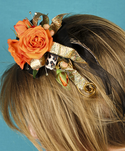This fun orange headpiece features fun orange flowers with gold & leopard print ribbon. Such a fun added detail to any prom dress.