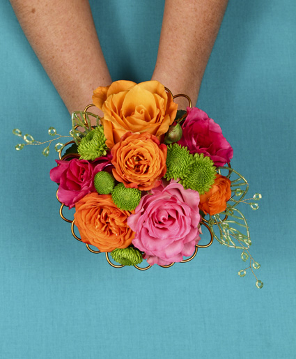 [Image: This fun and colorful hand held bouquet features orange, pink & green flowers with fun accents of wire.]