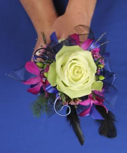 This fun prom bouquet features a single green rose with accents of fuschia flowers, purple ribbon, wire and feathers.