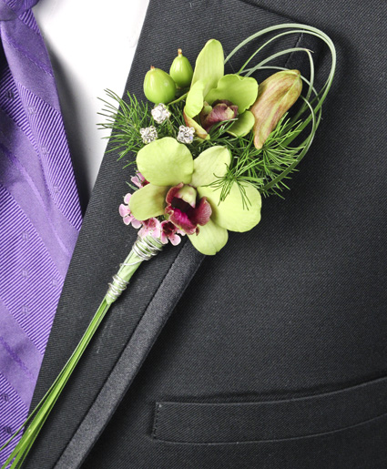 This green boutonniere features simple green flowers with unique greenery looping and crystal accents.]