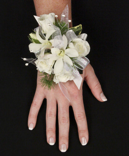 This beautiful white corsage is great for a wedding or prom. It features elegant white flowers with great details of pearls and greenery.