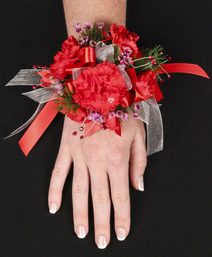 This red prom corsage features beautiful red flowers with red and white ribbon.]
